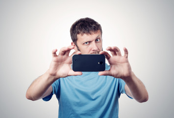 Funny bearded man photographed on a smartphone