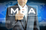 Businessman hand pointing to MBA sign on virtual screen poster