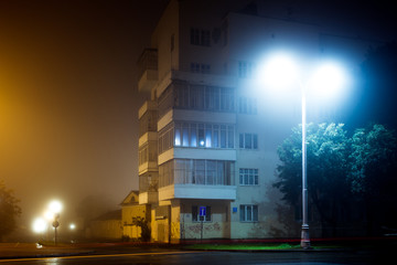 Apartment block on empty night city street covered with fog