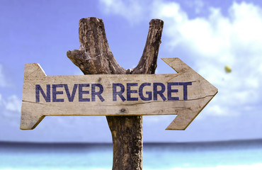 Never Regret wooden sign with a beach on background