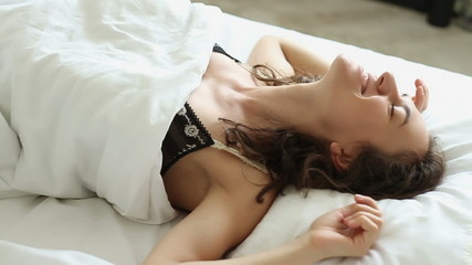 Woman falling backward onto bed, slow motion