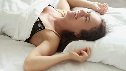 Woman falling backward onto bed, slow motion