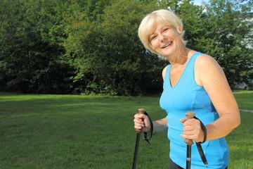 Dame beim Walken in der Natur mit Kopfhörer