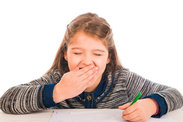 Cute little girl yawning while writing