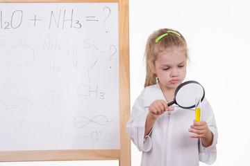 Chemist examines fluid, standing at the blackboard