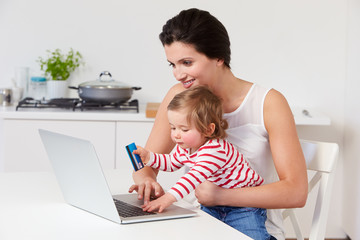 Mother With Child Using Laptop At Home