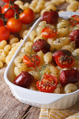 pasta baked with cheese, tomatoes and sausages vertical
