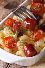 pasta baked with cherry tomatoes and sausage and fork close-up