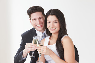Studio Portrait Of Couple Celebrating With Champagne