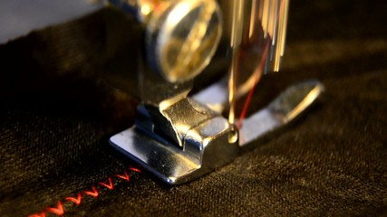 sewing machine and item of black clothing. Extreme macro