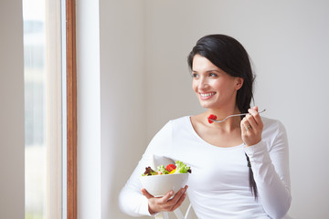 Woman Sitting In Chair Eating Bowl Of Fresh Salad