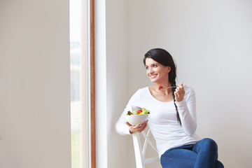 Woman Sitting In Chair Eating Bowl Of Fresh Fruit