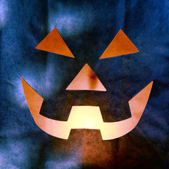 Glowing Jack o Lantern Face Cut from Paper Bag