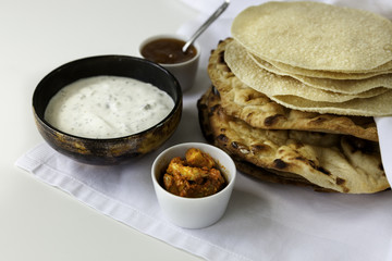 Flat indian breads with a pickle, chutney and raita