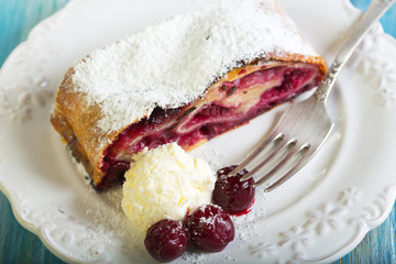Plate with cherry strudel closeup.