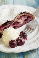 Plate with cherry strudel and fork on blue table.