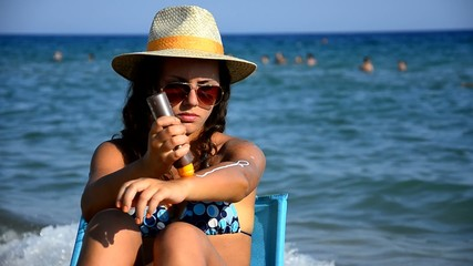 Girl with straw hat applying sun block cream on the beach