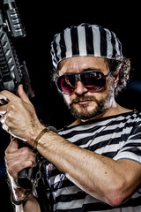 Criminal .Prison riot concept. Man holding a machine gun, prison