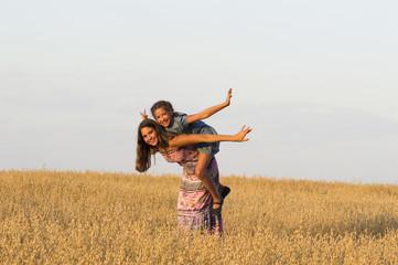 Two girls is  playing in oat field.