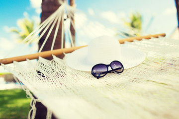 picture of hammock with white hat and sunglasses