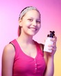 Teen girl holds bottle with water and smiling
