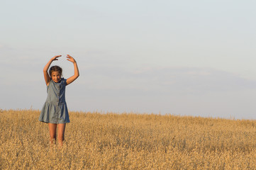 The girl is dancing in oat field.