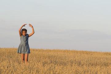 The girl is dancing in oat field.