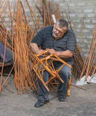 Master of wicker-work making a stool