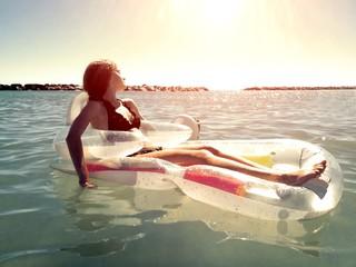 ragazza su canotto al tramonto in mare