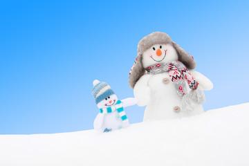 Happy winter snowmen family or friends against blue sky
