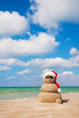 Sand snowman in santa hat. Holiday concept