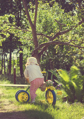 Vintage foto of Little child riding a bicycle on green grass