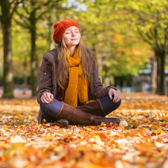 Girl sitting on the ground in park on a sunny fall day