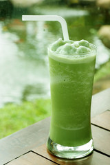 glass of green tea frappe on wooden table in garden.
