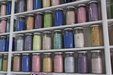 Shelving with glass jars of colorful pigments