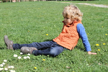 Blond Kid sitting on the grass - tuscany italy