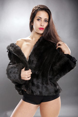 Cute brunette in fur jacket, shorts and not much else