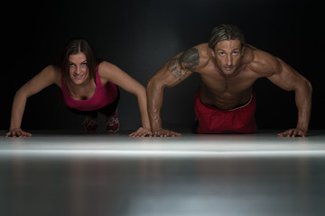 Couple Doing Pushups In A Studio
