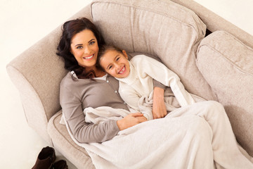 young girl and her mother lying on the couch