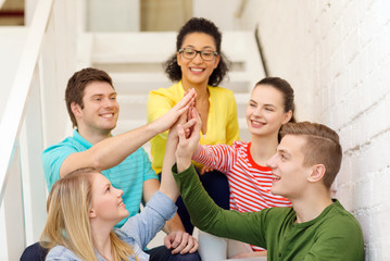 smiling students making high five gesture sitting