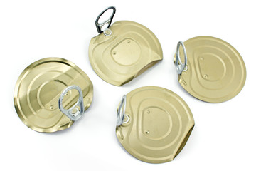 Four tin can lids with opener isolated on white