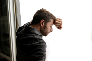 man on window suffering emotional crisis and depression