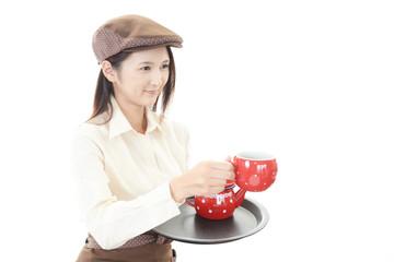 コーヒーを運ぶ笑顔のウェイトレス