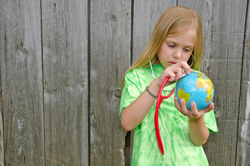young girl with stethoscope on globe