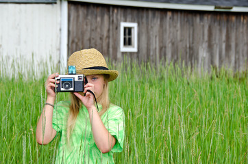 little girl with retro camera in field