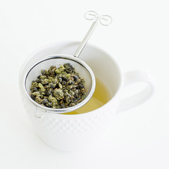 Herbal tea in a glass cup, metal sieve with dry herbal tea on a