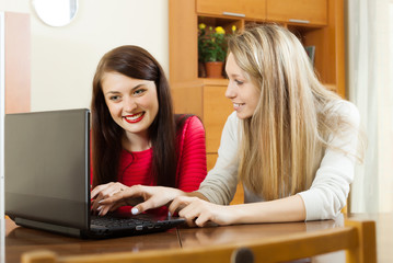 Happy women sitting at table with laptop