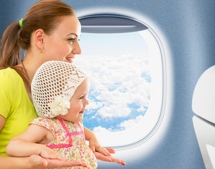 Happy mother and kid travelling together in airoplane cabin near