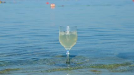 Glass of white wine by the coast.on the rocks, washed by the wav