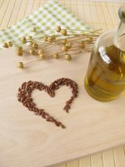 Ein Herz aus Leinsamen und eine Flasche Leinsamenöl